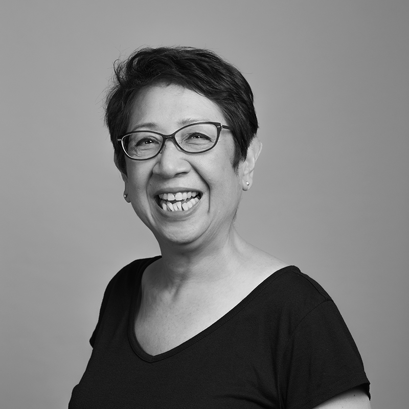 Image of Peggy Ferroa. A smiling woman wearing black glasses, wearing a black scoop-neck t-shirt.