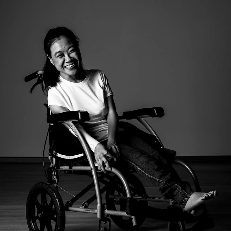 Image of Stephanie Fam. The photo shows a smiling woman in a wheelchair. She is wearing a white t-shirt and dark blue jeans.