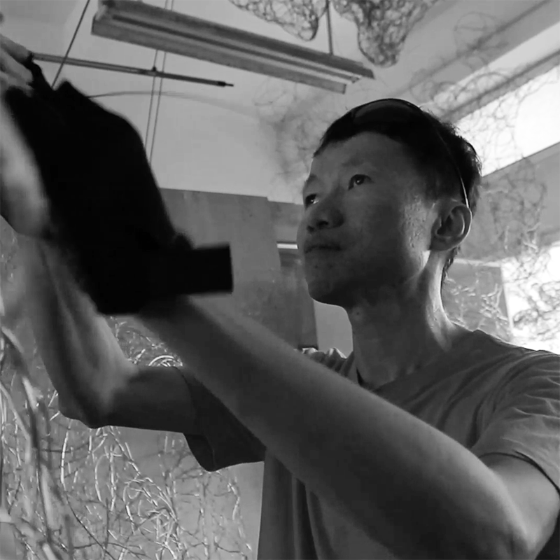 Image of visual artist Victor Tan. The image shows a man in a white t-shirt sculpting with wires